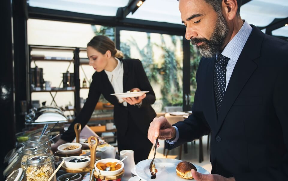 A business man and woman filling their plates with food during a meeting