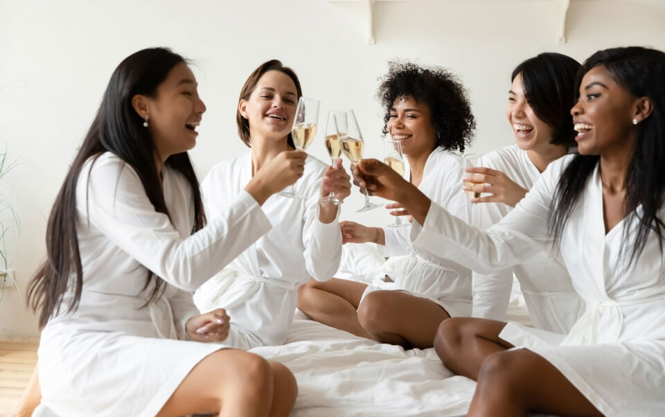 Group of women in white ropes drinking wine on a bed