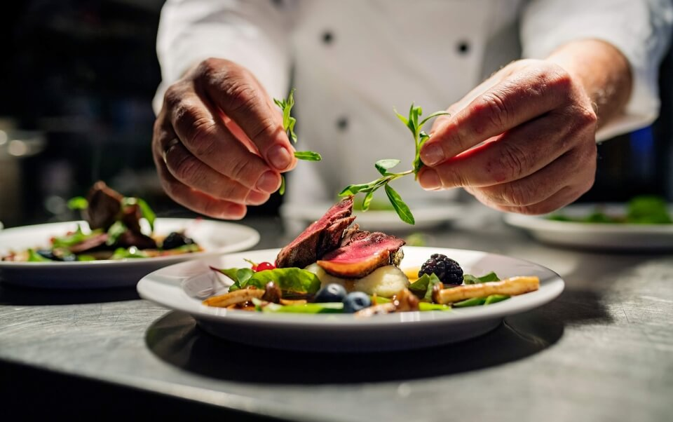 A chef at Signature Restaurant plating a meal