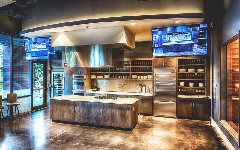 The view of a modern kitchen with TV screens and stainless steel appliances